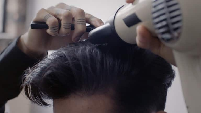 A dark haired guy blow drying his hair.
