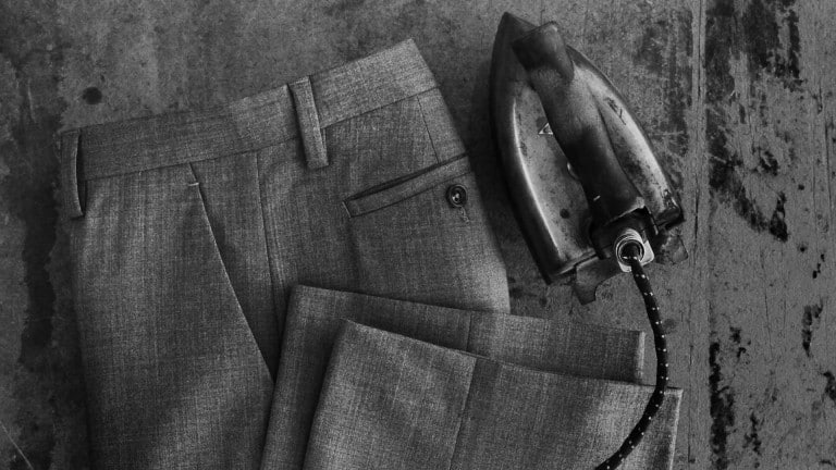 Freshly ironed dress trousers next to an old iron.