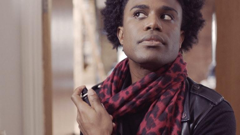 A man, in a scarf, spraying fragrance.