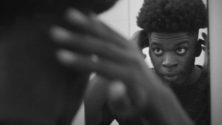 A young guy, combing his afro with a wide-tooth comb.